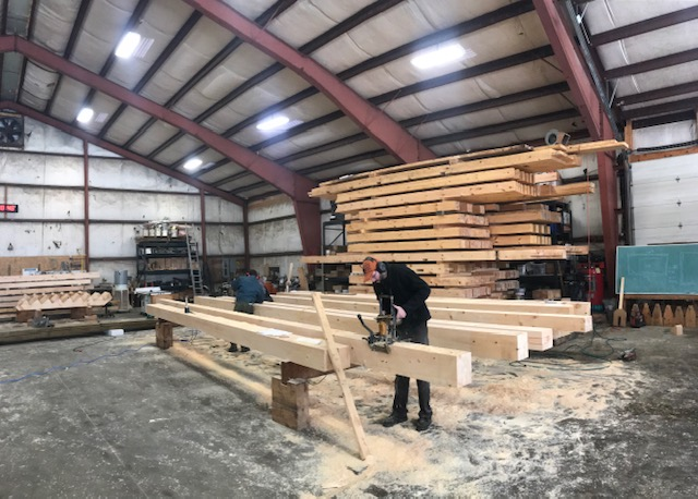 Working on the beams for a custom designed building built at the Shelter Institute